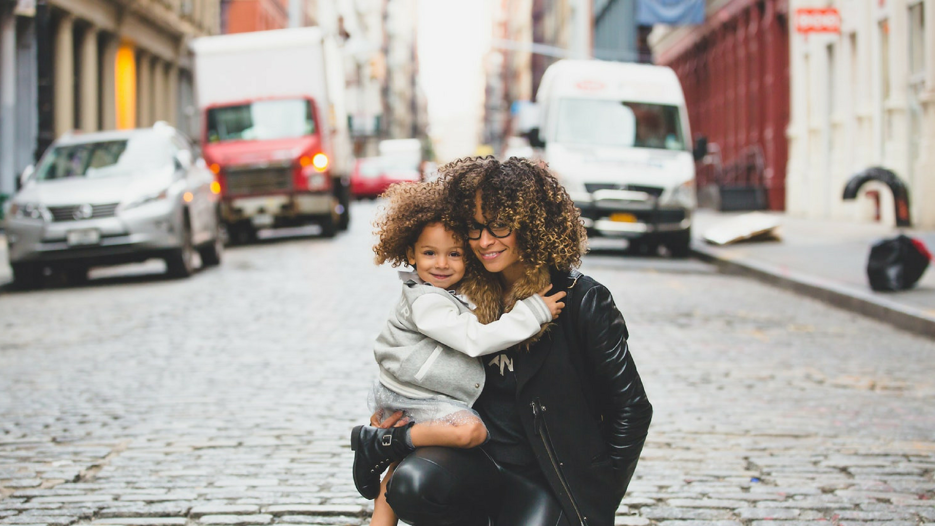 woman and confident child sitting on road
